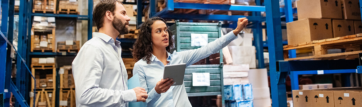 Two warehouse managers discussing recent purchase orders by retailers.